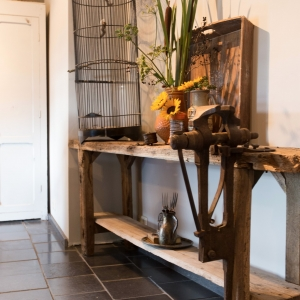 Heritage Black Anticato. Natuursteen tegels in landelijke keuken. Houten bank met vogelkooi