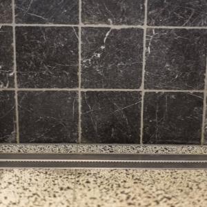 Efesus Marmer Zwart Soft Finish met drain in terrazzo tegels.