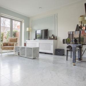 Bianco Carrara Type C Gezoet. Woonkamer met vierkante marmer tegels.