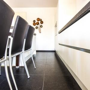 Graniet Coffee Brown Leather Finish in witte keuken met zwart leren stoelen.
