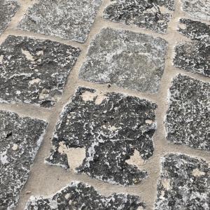 Kleine Kerkdallen in halfsteensverband. Cementgrijs gevoegd. Lesiteen met ruw oppervlak