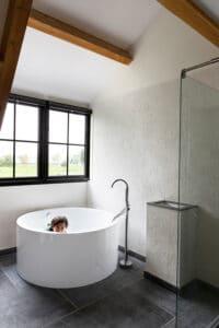 kind-in-bad-bij-badkamer-belgisch-hardsteen-raamzaag-gezaagd-vloertegels-tegelvloer